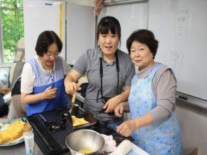 韓国人女性(中央)と卵焼きを作る生徒の女性