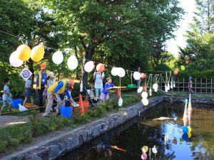日本庭園の池の的めがけて水鉄砲を撃つ