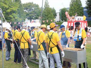 そろいの黄色いTシャツで焼き鳥を焼く男性陣=里塚緑ヶ丘町内会
