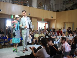 モデルをエスコートするのは、イベントの呼びかけ人で札幌里塚病院の松永先生(右)