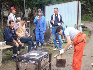 ハウスの外でサンマを焼く。中央が吉田さん