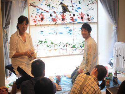 店主の出町南さんの詩の朗読に合わせてI絵を描く近藤さん(右)