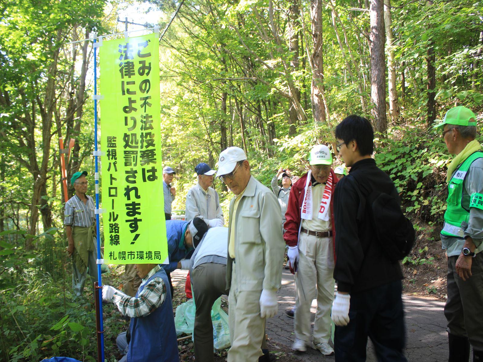 ゴミ不法投棄禁止ののぼりを立てる地域住民