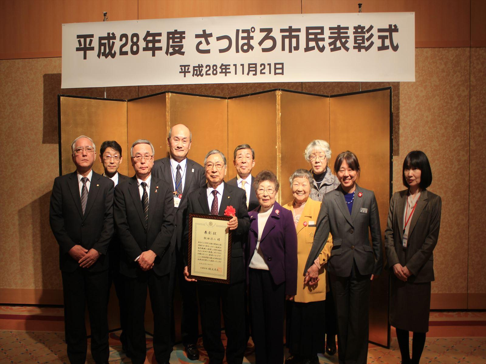 札幌市自治振興功労者の表彰を受けた飯田さん(中央)と祝福する皆さん